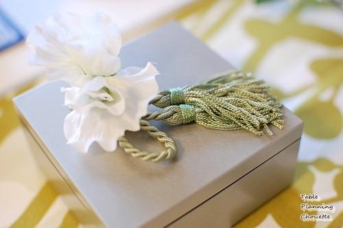 お重の上にタッセルと白い花